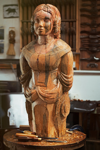 A carved wooden female ship's figurehead on a bench in a workshop with a pattern of wood grain markiの写真素材 [FYI02259814]