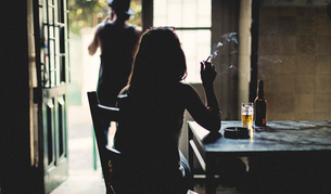 Rear view silhouette of woman sitting indoors at a table, smoking cigarette, beer glass and bottle oの写真素材 [FYI02259823]