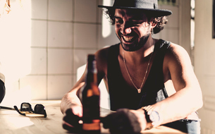 Bearded man wearing hat sitting indoors at a table, beer bottle in foreground.の写真素材 [FYI02259831]