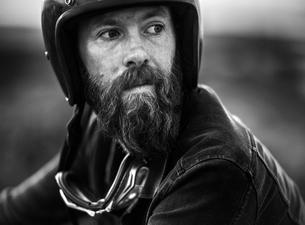 Portrait of bearded man wearing open face crash helmet, goggles round his neck.の写真素材 [FYI02259855]