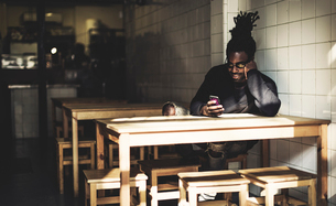 Man with dreadlocks sitting indoors at a table, looking at smartphone, beer bottle on the table.の写真素材 [FYI02259862]