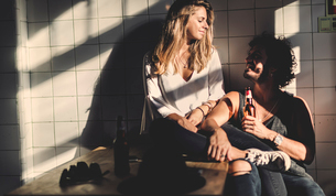 Man with brown hair holding beer bottle and a woman with long blond hair sitting indoors, looking atの写真素材 [FYI02259888]
