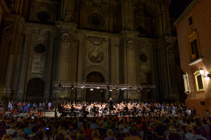 Audience listening to music performed by classical orchestra, open air concert at night.の写真素材 [FYI02259897]
