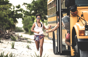 A young woman chasing after a moving school bus.の写真素材 [FYI02259960]