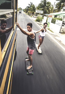 Two young people skateboarding while holding on to a moving school bus.の写真素材 [FYI02259966]
