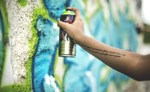 Close up of a person spray painting a graffiti  tag onto a wall.の写真素材 [FYI02259980]