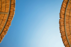 Low angle view of two straw parasols against a clear blue sky on a Greek island.の写真素材 [FYI02259986]