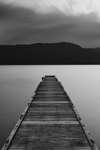 Wooden pier stretching out into the water at Towada Lake with mountains in the distance.の写真素材 [FYI02259993]