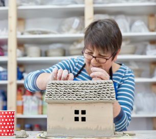 A woman potter using a small shaping tool to create the roof details for a clay model of a house.の写真素材 [FYI02260004]