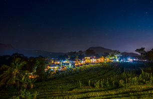 Night view of Bali Island, view across fields and hillside, to a lighted village.の写真素材 [FYI02260011]