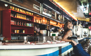 Side view of woman wearing jeans and sleeveless top leaning against a bar counter in a restaurant, lの写真素材 [FYI02260014]
