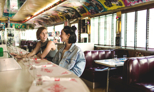 Two young women sitting side by side at a bar counter in a diner.の写真素材 [FYI02260025]