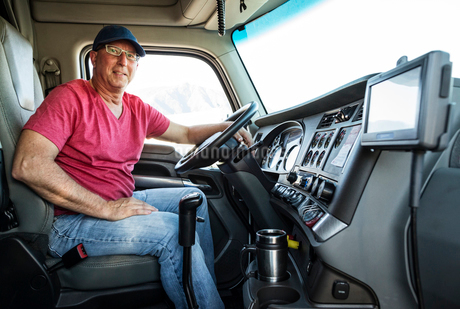 Caucasian man truck driver in the cab of his commercial truck.の写真素材 [FYI02260082]