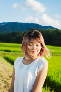 A young woman in a white shirt, hair blown in the wind, standing in open space by rice paddy fields.の写真素材 [FYI02260096]