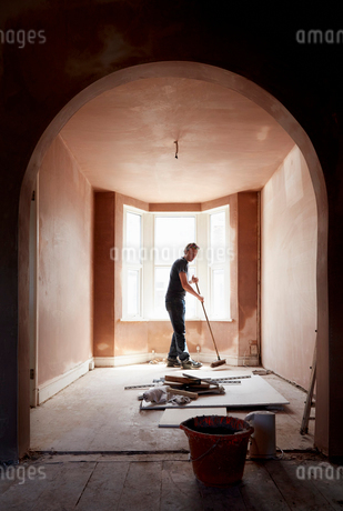 A builder sweeping and tidying up in a renovated replastered house with an archway.の写真素材 [FYI02260097]