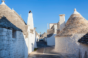 Traditional white washed round stone houses with conical roofs lining Mediterranean street.の写真素材 [FYI02260098]