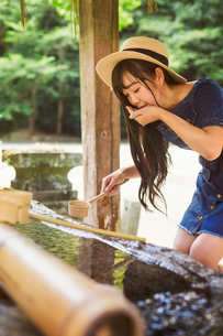 Young woman wearing blue dress and hat using bamboo water hand washing basins at Shinto Sakurai Shriの写真素材 [FYI02260106]