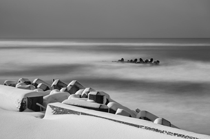 Snow-covered wave breakers on a rocky beach in winter.の写真素材 [FYI02260108]
