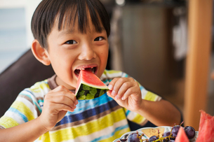 Close up of boy with black hair wearing stripy T-shirt eating a slice of watermelon.の写真素材 [FYI02260113]