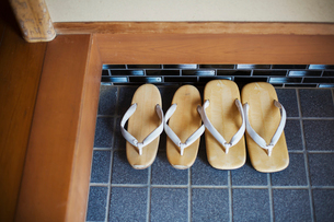 High angle view of two pairs of traditional Japanese sandals on a blue tiled floor.の写真素材 [FYI02260122]