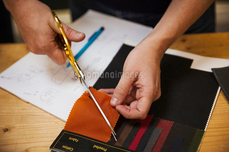A person using shears to cut a fabric sample at a workbench, overhead view.の写真素材 [FYI02260123]