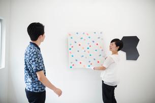 Man wearing blue shirt watching woman hang modern painting on white wall in art gallery.の写真素材 [FYI02260128]