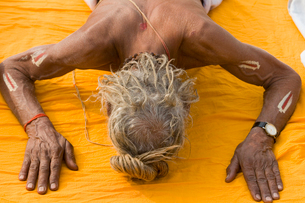 High angle view of shirtless man with grey hair lying on his front on a yellow cloth, outstretched aの写真素材 [FYI02260151]