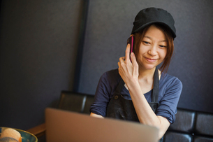 Woman working in a bakery, wearing baseball cap, sitting at table in front of laptop, using mobile pの写真素材 [FYI02260177]