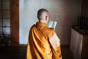 Rear view of Buddhist monk with shaved head wearing golden robe sitting indoors in a temple, holdingの写真素材 [FYI02260182]