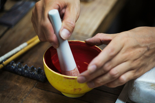 Close up of person working in a Japanese porcelain workshop, mixing red paint with pestle and mortarの写真素材 [FYI02260189]