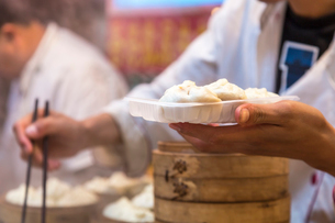 Close up of person holding plate with dumplings and chopsticks.の写真素材 [FYI02260196]