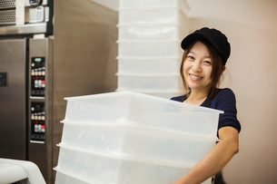 Woman working in a bakery, wearing baseball cap, carrying stack of white plastic crates.の写真素材 [FYI02260211]