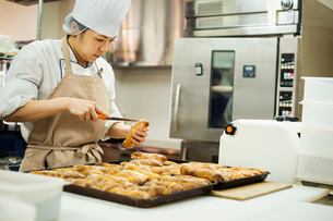 Woman wearing chef's hat and apron working in a bakery, slicing freshly baked rolls on large trays.の写真素材 [FYI02260222]
