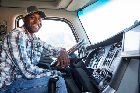 Black man truck driver in the cab of his commercial truck.の写真素材 [FYI02260229]
