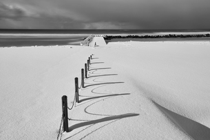 Fence running along a snow-covered beach near the ocean in winter.の写真素材 [FYI02260231]
