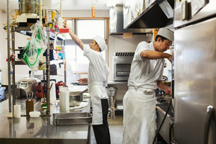 Two chefs working in the kitchen of a Japanese sushi restaurant.の写真素材 [FYI02260244]