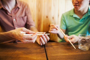 Two people, a Japanese man showing a Western man how to use chopsticks in a noodle shop.の写真素材 [FYI02260247]