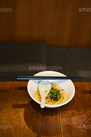 High angle close up of bowl of soup with spoon and pair of chopsticks on table.の写真素材 [FYI02260252]