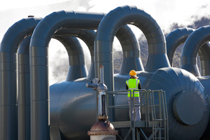 Rear view of woman engineer standing on a platform at a Geothermal Plant.の写真素材 [FYI02260262]