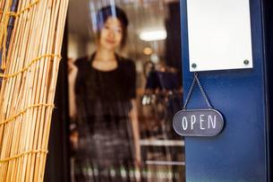 Open sign on glass door to a bakery, a woman standing in the doorway.の写真素材 [FYI02260267]