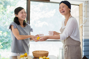 Two smiling women standing indoors at a table, holding drinking glasses.の写真素材 [FYI02260271]