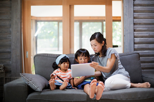 Woman, boy and young girl sitting on a grey sofa, looking at digital tablet.の写真素材 [FYI02260276]