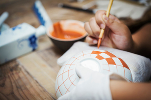 Close up of person working in a Japanese porcelain workshop, painting geometric pattern onto white bの写真素材 [FYI02260278]