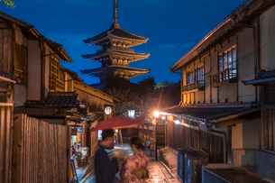 Japanese couple in traditional dress standing in a street at night, a pagoda in the background.の写真素材 [FYI02260283]
