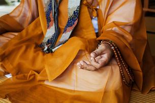 Close up of Buddhist monk wearing golden robe sitting cross legged on the floor, meditating, Buddhisの写真素材 [FYI02260284]