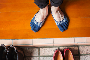 A man's feet in socks by a row of shoes.の写真素材 [FYI02260288]