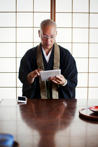 Buddhist monk with shaved head wearing black robe sitting indoors at a table, using digital tablet.の写真素材 [FYI02260293]