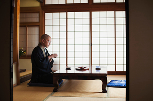 Side view of Buddhist monk with shaved head wearing black robe kneeling indoors at a table, holdingの写真素材 [FYI02260295]