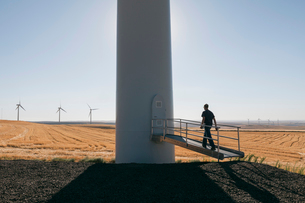 A wind farm technician standing and using a laptop at the base of a turbine on a wind farm in open cの写真素材 [FYI02260297]