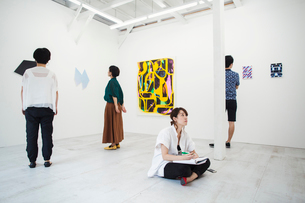 Woman with black hair sitting on floor in art gallery with pen and paper, looking at modern paintingの写真素材 [FYI02260299]